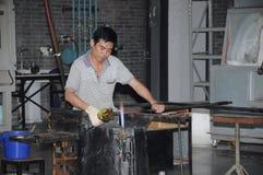 Kinesisk man som formar varmt exponeringsglas för att blåsa Fotografering för Bildbyråer