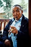 Kinesisk man som i stillhet röker ett långt rör med en cigarr under eftermiddagvärmen arkivfoto