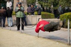 Kinesisk man som vilar i en ovanlig väg Arkivbild