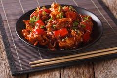 Kinesisk mat: griskött i sås med grönsaker på en platta horizont arkivbild