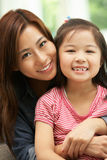 Kinesisk moder och dotter som sitter på sofaen Royaltyfri Foto
