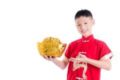 Kinesisk pojke i den röda traditionella klänningen som rymmer guld- pengar Royaltyfri Foto