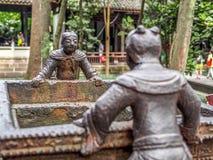 Kinesisk skulpturstaty i den nära fokusen, grund DOF Arkivbilder