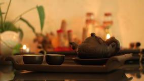 Kinesisk tekanna och kopp på trämagasinet för traditionell teceremoni Traditionell tekruka för japansk ceremoni på bränning lager videofilmer