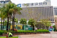 Kinesisk trädgårdsmästare på arbete framme av China Construction Bank royaltyfri foto