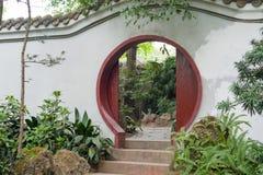 Kinesisk traditionell rund dörr på en vit vägg royaltyfri foto