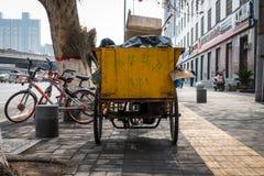 Kinesisk vagn för avfallsamling som parkeras på trottoaren under Wor Fotografering för Bildbyråer