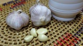 Kinesisk vitlök och en vitlökstansmaskin arkivfoton
