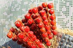 Kinesiska äpplen på en pinne söt godis Arkivbild