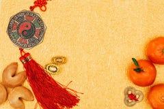 Kinesiska amuletter med tangerin och förmögenhetkakor på guld- yttersida, kinesiskt begrepp för nytt år Royaltyfri Bild