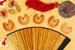 Kinesiska amuletter och förmögenhetkakor på guld- yttersida, kinesiskt begrepp för nytt år Royaltyfri Foto