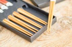 Kinesiska bambupinnar i svart ask på träbakgrund Royaltyfri Foto