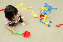 Kinesiska barn som spelar på den inomhus sandlådan Arkivbild
