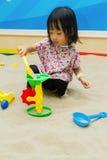 Kinesiska barn som spelar på den inomhus sandlådan Arkivbilder