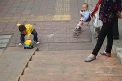 Kinesiska barn som spelar på trottoaren Arkivbilder