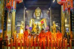 Kinesiska buddistiska munkar som tänder stearinljusen Fotografering för Bildbyråer