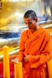 Kinesiska buddistiska munkar som tänder stearinljusen Arkivfoto