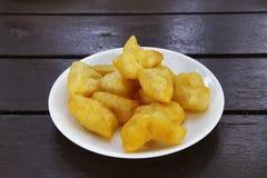 Kinesiska djupa Fried Dough Sticks tjänade som i den vita plattan på den wood tabellen Arkivbilder