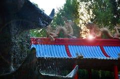 Kinesiska drakar, statyer av ronin och springbrunnar på solnedgången royaltyfria foton