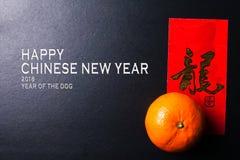 Kinesiska festivalgarneringar för det nya året, röda paket och mandariner, guld- kinesiskt bokstavshjälpmedel lyckas arkivbild