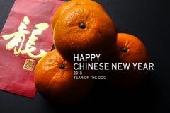 Kinesiska festivalgarneringar för det nya året, röda paket och mandariner, guld- kinesiskt bokstavshjälpmedel lyckas arkivfoto