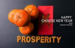 Kinesiska festivalgarneringar för det nya året, röda paket och mandariner, guld- kinesiskt bokstavshjälpmedel lyckas arkivfoton