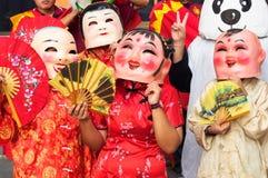 Kinesiska festivalstudenter för nytt år bär kines Lucky God Masks till deltagaren i festival Arkivfoton