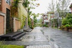 Kinesiska gammalmodiga byggnader längs gatan på regnig dag Fotografering för Bildbyråer