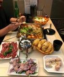 Kinesiska klimpar, rått kött, rå grodaben på tabellen som förbereds för själv-matlagning på en induktionsugn i buljong i en kines arkivbild