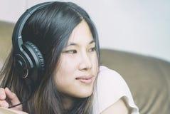 Kinesiska kvinnor är lyssnar till musikheadphonen arkivfoton