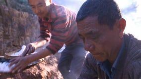 Kinesiska män kokar saltar, kristalliserat att svepa saltar från kokt saltvattens- och att arbeta på saltar fältet yunnan Kina arkivbild