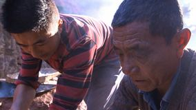 Kinesiska män kokar saltar, kristalliserat att svepa saltar från kokt saltvattens- och att arbeta på saltar fältet yunnan Kina royaltyfri bild