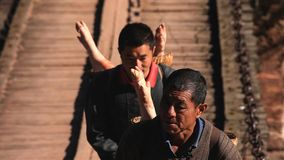 Kinesiska män som bär svinet i bygdmarknad yunnan Kina royaltyfria foton
