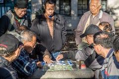 Kinesiska män som spelar brädeleken Royaltyfri Foto