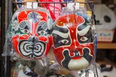 Kinesiska maskeringar i en souvenir shoppar på den Yokohama kineskvarteret Arkivbilder