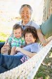 Kinesiska morföräldrar i hängmatta med barnbarnet för blandat lopp arkivbilder