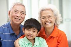 Kinesiska morföräldrar med sonsonen som kopplar av på Hom Royaltyfria Bilder