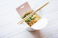 Kinesiska nudlar i takeaway ask på träbakgrund Mat Arkivfoto