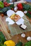Kinesiska nudlar wokar in asken Arkivbild