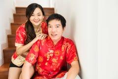 Kinesiska par klär den röda cheongsamdräkten i hus arkivbilder