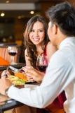 Kinesiska par som har den romantiska matställen i utsmyckad restaurang Royaltyfri Foto