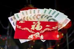 Kinesiska pengar för nytt år i röd kuvertgåva Arkivbild