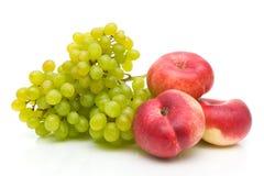 Kinesiska plana persikor och gröna druvor på white Arkivfoto