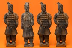 4 kinesiska terrakottakrigare mot en ljus apelsin b royaltyfri foto