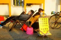Kinesiska unga kvinnor i gatorna som fullständigt gör öron, varje laddning 15 yuan Fotografering för Bildbyråer