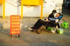 Kinesiska unga kvinnor i gatorna som fullständigt gör öron, varje laddning 15 yuan Royaltyfri Bild