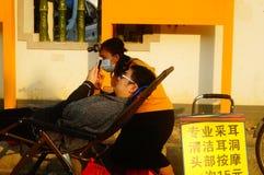 Kinesiska unga kvinnor i gatorna som fullständigt gör öron, varje laddning 15 yuan Royaltyfri Foto