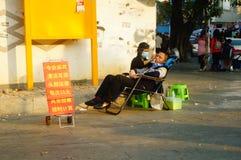 Kinesiska unga kvinnor i gatorna som fullständigt gör öron, varje laddning 15 yuan Arkivfoto