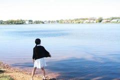 Kinesiskt flickabarn som kastar stenen i vattnet Fotografering för Bildbyråer