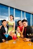 Kinesiskt folk som dricker coctailar i lyxig coctailstång Arkivfoto